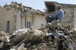 In this 2009 file photo, a man sits on rubble in the village of Onna, a day after a powerful earthquake struck the Abruzzo region in central Italy.