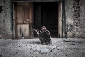In this Oct. 24 photo, a Free Syrian Army fighter sights a government  position as rebel fighters belonging to the Liwa Al Tawhid group carry out a military operation.
