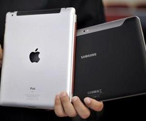 In this 2011 file photo, an attorney holds an Apple iPad, left, and a Samsung Galaxy Tab 10.1 at the regional court in Duesseldorf, Germany.