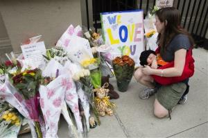 A woman looks at a memorial outside the apartment building where the two children were killed.