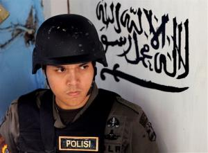 An Indonesian police officer stands guard at the door of the house of a suspected terrorist after a raid in Jakarta, Indonesia, Saturday, Oct. 27, 2012.