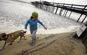 Jenny Lind and her dog Greta run away from a wave that comes up the beach as Hurricane Sandy bears down on the East Coast, Sunday, Oct. 28, 2012, in Ocean City, Md.