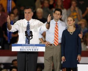 Mitt Romney speaks as running mate Rep. Paul Ryan, R-Wis., and his wife Janna listen during a campaign rally at the Marion County Fairgrounds in Marion, Ohio, Sunday, Oct. 28, 2012.