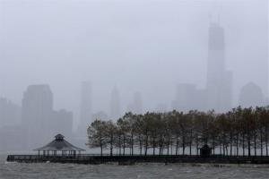 One World Trade Center, right, peeks through a light rain as water from the Hudson River creeps up on Pier A Park with the expected arrival of Hurricane Sandy in Hoboken, NJ, Monday, Oct. 29, 2012.