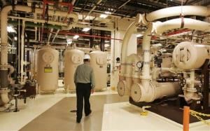 An Exelon employee walks past equipment in the turbine building at the Oyster Creek nuclear plant in this file photo.