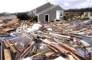 Debris floats around a house pushed off its foundation in the aftermath of superstorm Sandy in East Haven, Conn., Tuesday.