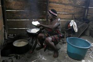 A Nigerian woman processes cassava root into flour.
