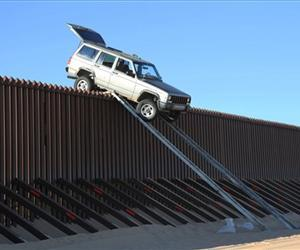 A Jeep Cherokee that smugglers were attempting to drive over the US-Mexico border fence is seen stuck at the top of a makeshift ramp near Yuma, Ariz.
