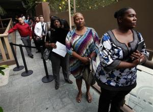In this Friday, Aug. 17, 2012 file photo, Sheila Bird, right, waits in line for employment interviews at a job fair at City Target in Los Angeles.