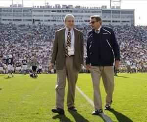Then-Penn State President Graham Spanier and then-head coach Joe Paterno chat before a game against Iowa in State College, Pa, Oct. 8, 2011.