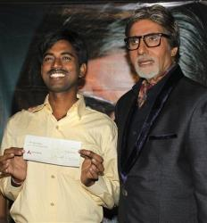 Sushil Kumar, left, with Bollywood actor Amitabh Bachchan, shows $1 million check after winning on an Indian game show, in Mumbai, India, on Oct. 25, 2011.