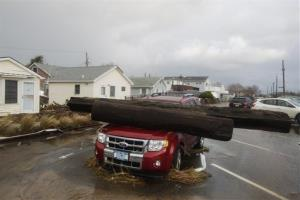 A log rests on a vehicle damaged by superstorm Sandy at Breezy Point in the New York City borough of Queens Tuesday.