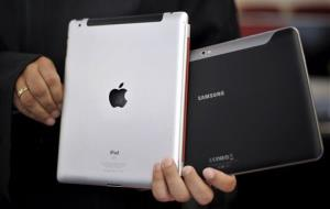 An attorney holds an Apple iPad, left, and a Samsung Galaxy Tab 10.1.