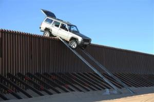 In this photo provided by the U.S. Customs and Border Protection, a silver Jeep Cherokee that suspected smugglers were attempting to drive over the U.S.-Mexico border fence is stuck.