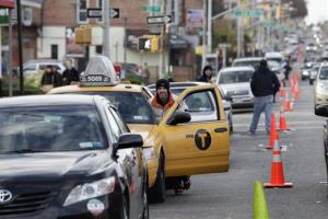 A cab driver pushes his taxi cab forward in a line for gasoline in the Brooklyn borough of New York, Friday, Nov. 2, 2012.