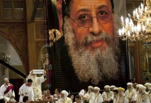 Acting Coptic Pope Pachomios displays the name of new Pope Tawadros II, depicted in the large poster, at the Coptic Cathedral in Cairo, Egypt, Sunday, Nov. 4, 2012.