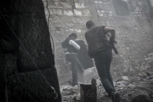 In this Saturday, Nov. 03, 2012 photo, rebel fighters run for cover through smoke from an explosion as they try to repel a coordinated attack using mortar, tank and aerial artillery fire by loyalists to President Bashar Assad in the Jedida district of Aleppo, Syria.