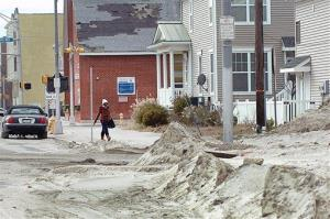 A woman walks through sand on the corner of Atlantic and St. Katherine's Place in Atlantic City, NJ, Saturday, Nov. 3, 2012.