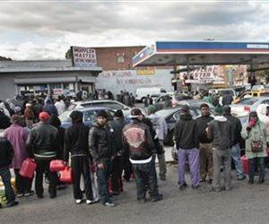 Gas customers on foot with portable containers and lines of vehicles wait for gas pumps to open at a service station, Nov. 3, 2012 in the Brooklyn borough of New York.
