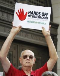 Mike Griffith, of Canton, Ga., holds a sign during a protest against President Barack Obama's health care reform plan outside the  11th Circuit Court of Appeals in Atlanta, Wednesday, June 8, 2011.