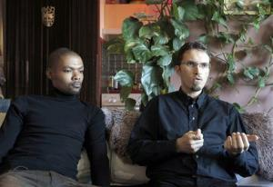 In this Monday, Oct. 22, 2012 photo, Ludovic-Mohamed Zahed, right, and his live-in partner Qiyaammudeen Jantjies, who are married in South Africa, sit side-by-side in Sevran, France, outside Paris.