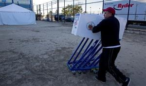 A worker pushes voting machines to tents that have become makeshift voting locations in the Rockaway neighborhood of Queens, New York City.