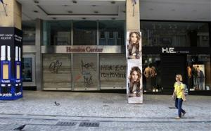 A woman walks past closed shops at the main commercial Athens' Ermou street on Tuesday Nov. 6, 2012.