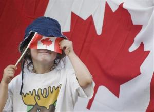 A young girl hides behind a small Canadian flag during the annual Canada Day parade in Montreal, Sunday, July 1, 2012.