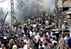 This photo released by the Syrian official news agency SANA, shows Syrians standing at the scene after a blast occurred according to footage and reports shown on State-run Al-Ikhbariya television.