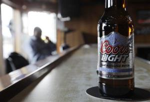 A Coors Light sits on the bar as a patron sips a beer at a tavern Monday, May 4, 2009, in Blue Island, Ill.