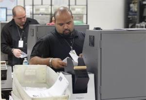 Workers scan in absentee ballots at the Miami-Dade County Elections Department Tuesday.