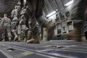 In this Dec. 17, 2011, photo, US Army soldiers from the 25th Infantry Division board a plane at Camp Adder moments before the unit leaves Iraq.