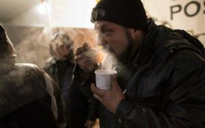 Benny Roman, volunteer and 30-year resident of Rockaway Park in Queens, warms up as he eats soup at an outreach center with members of Occupy Sandy.