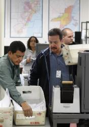 Workers prepare to scan in boxloads of absentee ballots at the Miami-Dade County Elections Department Tuesday in Doral, Fla.