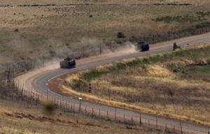 Israeli army armored vehicles drive along the border between Israel and Syria in the Golan Heights in this Monday, July 23, 2012, file photo.