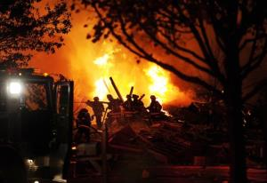 Authorities say a loud explosion has leveled two homes in Indianapolis and set a dozen others ablaze in a neighborhood, killing at least two people.
