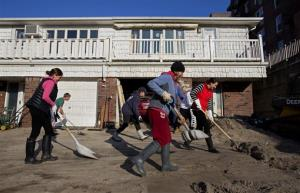 Neighbors volunteering to help another neighbor in need move deep sand from the house on Beach 121 Street in the Rockaway Park neighborhood of the borough of Queens, New York, Sunday, Nov. 11, 2012.