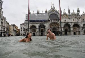A young man and a woman enjoy swimming in flooded St. Mark's Square in Venice, Italy, Sunday, Nov. 11, 2012.