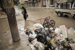 In this Saturday, Nov. 10, 2012 photo, a women passes accumulated garbage in the Bustan al-Qasr area of Aleppo, Syria. Due the heavy fighting and shelling, the garbage collection system collapsed weeks ago.