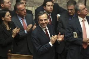 Greece's Prime Minister Antonis Samaras and his party's lawmakers applaud after voting on the country's 2013 budget in Athens, early Monday, Nov. 12, 2012.