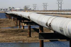 In this 2007 file photo, a new oil transit pipeline runs across the tundra to flow station at the Prudhoe Bay oil field on Alaska's North Slope.