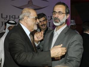 Syrian opposition figure and prominent Syrian human rights activist Haytham al-Maleh, left, congratulates Islamic preacher Maath al-Khatib, in Doha, Qatar on Sunday, Nov. 11, 2012.