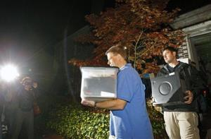 FBI agents carry boxes and a computer from the home of Paula Broadwell Monday night.