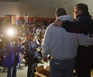 Chris Christie stands is arm-in-arm with Keansburg, NJ, Mayor George Hoff as he addresses residents inside the Joseph Bolger Middle School, where residents were able to get a hot meal, Nov. 5, 2012.