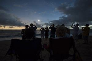 People gather on Palm Cove beach in Queensland state, Australia, to watch the total solar eclipse.