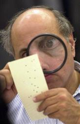 This 2009 file photo shows a Broward County canvassing board member examining a disputed ballot.
