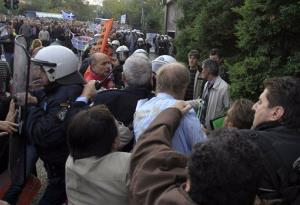 A protester punches the German consul in Thessaloniki, Wolfgang Hoelsche-Obermaier, as he arrives to attend a conference of Greek and German mayors in Thessaloniki, Nov. 15, 2012.