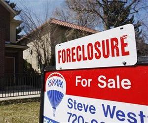 In this April 4, 2010 file photo, a forclosure sign tops the for sale sign outside a home in Denver.