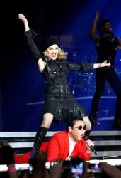 In this Nov. 13, 2012 photo released by Guy Oseary, singer Madonna, left, performs onstage with South Korean rapper PSY during Madonna's MDNA concert at Madison Square Garden in New York.
