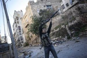 In this photo shot Wednesday, a Syrian rebel fighter aims at government forces during skirmishes in Aleppo, Syria.